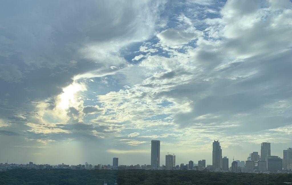 光る雲、ビル群と森の神宮前